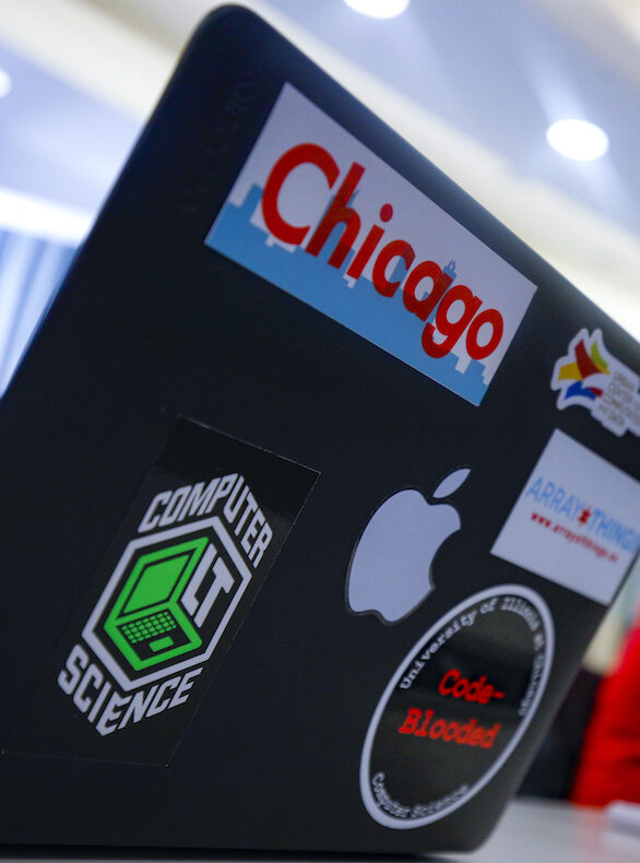 A laptop decorated with stickers relating to coding and the city of Chicago