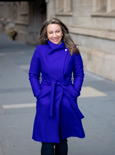 Reem Jaghlit, head of diversity, equity, and inclusion for ActiveCampaign, wears a bright blue coat on the sidewalk in front of a building.